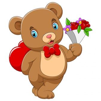 赤いハートと手に花を持つかわいいクマ