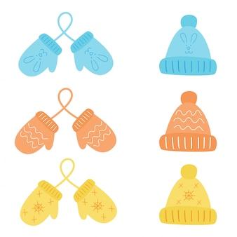 Красочный набор пар варежки и зимние шапки.