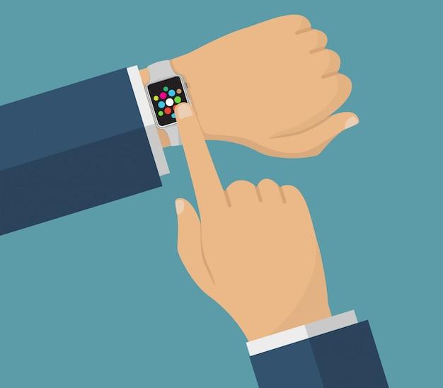 スマートな時計と人間の手。スマートウォッチでの操作。