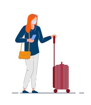 旅行者の女性。コロナウイルスのパンデミック中にバッグ、携帯電話、荷物ホイールスーツケースを保持しているマスクのツーリストの女性。