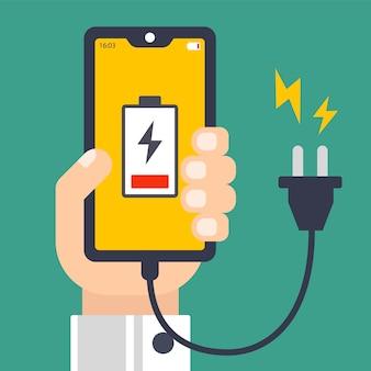 手が放電された携帯電話を保持しています。充電用コード。