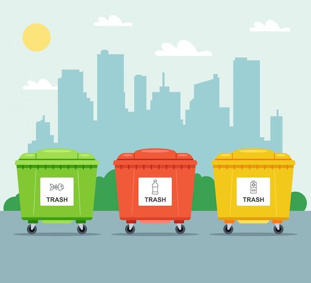Разноцветные урны для раздельного сбора мусора на фоне города.
