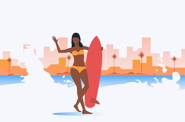 Темнокожая девушка держит доску для серфинга