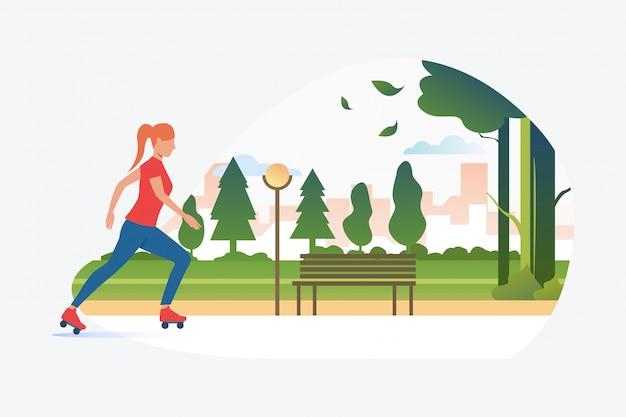 遠くの建物がある公園でスケートをする女性