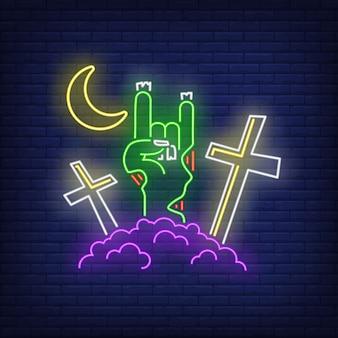 悪魔の角のゾンビの手ジェスチャーのネオンサインと墓地