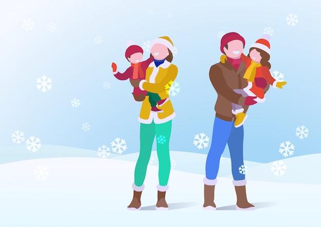 Счастливая семья, отец и мать, держа сына и дочь в зимней одежде