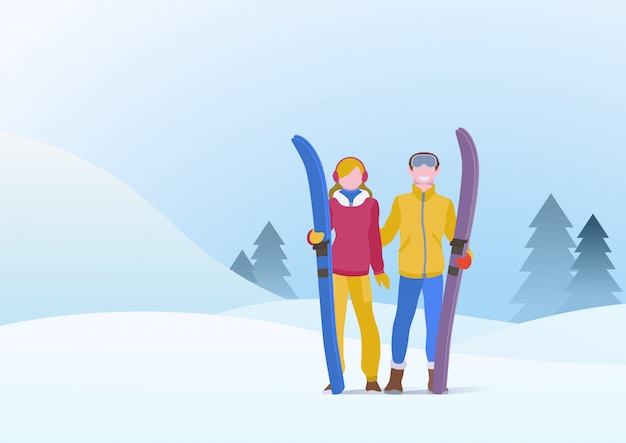 Пара мужчина и девушка, стоя с лыжами
