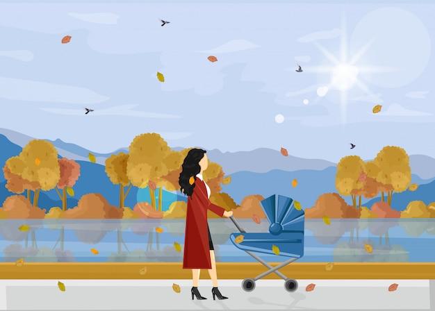 公園秋の散歩で赤ちゃんを持つ女性