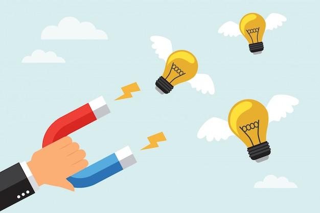 ビジネスマンは大きな磁石で電球を引き付ける