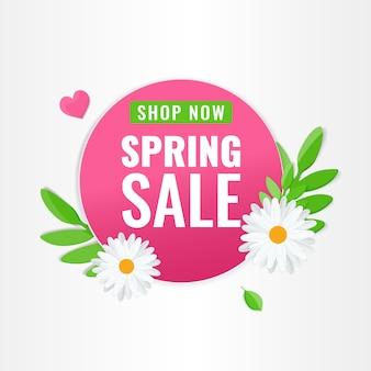 Круглый розовый баннер для весенней распродажи с цветами ромашки и зелеными листьями