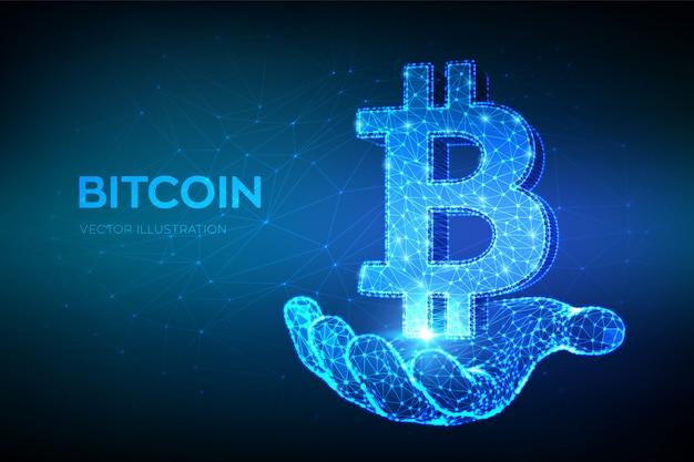 ビットコイン。低ポリゴンの抽象的なメッシュラインとポイントビットコインサインイン手に。暗号通貨。