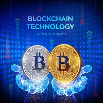 ビットコイン。手でビットコインシンボルと黄金と銀のコイン