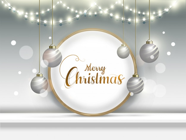 Текст каллиграфии с рождеством в круглая рамка с висящими безделушки и гирляндами освещения, украшенные на сером боке.