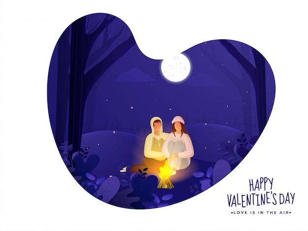 Молодые любящие пары сидя перед костром на отрезанной бумаге предпосылке сцены ночи природы в форме сердца для счастливого торжества дня валентинки.