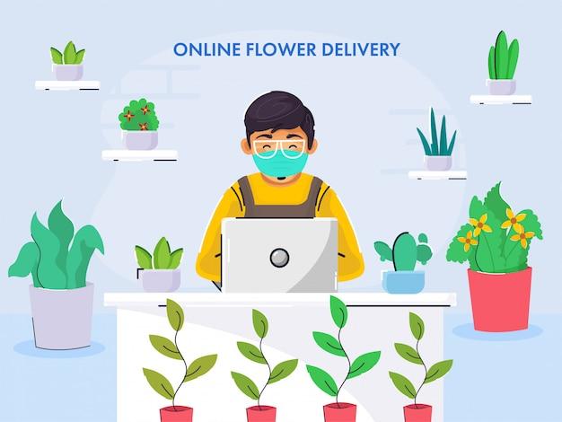 若い男の子は、花と机の上のラップトップで働く医療用マスクとオンライン花配達の概念のための青色の背景に植木鉢を着用します。