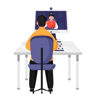 テーブルでデスクトップから女性にビデオ通話をしている男性の背面図。