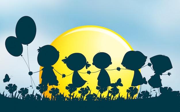 公園に手を持つ子供たちのシルエット