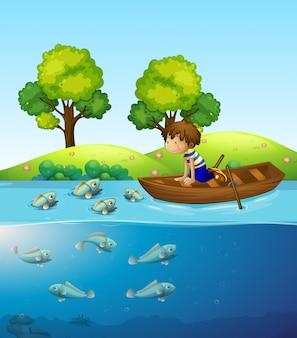 Мальчик на лодке, наблюдающий за рыбой