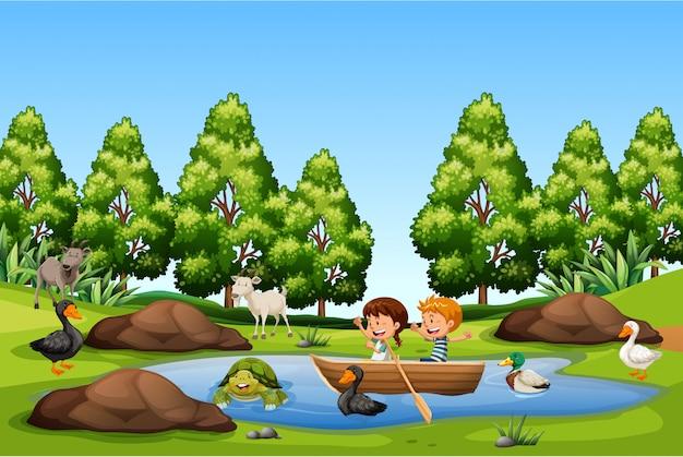 子供たちは湖の中でボートを漕ぐ
