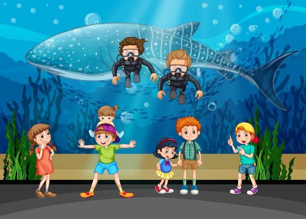 Дети смотрят на китов и дайверов в аквариуме