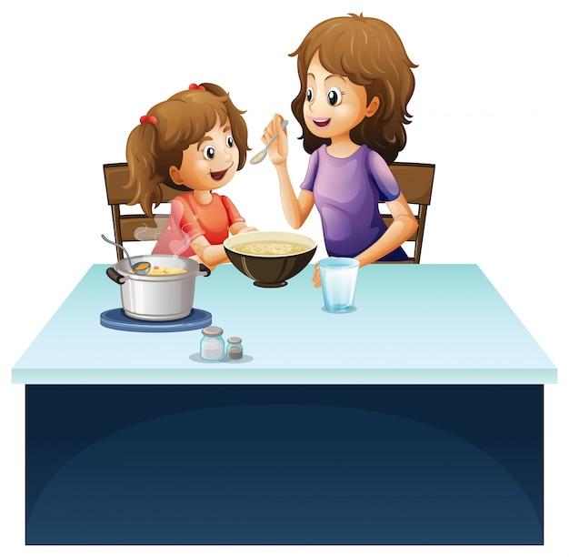 テーブルの上の小さな子供に餌をやる母
