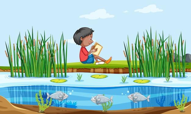 Мальчик читает книгу на природе