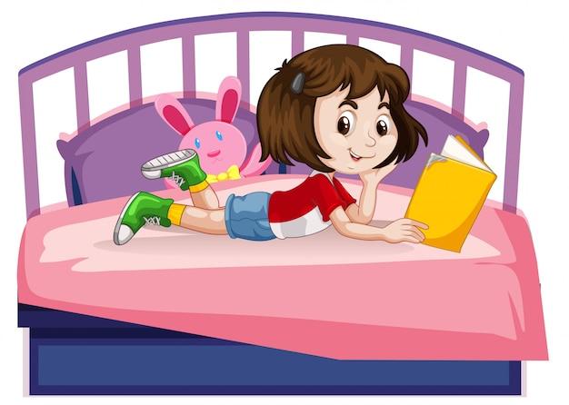 若い女の子がベッドの上の本を読んで