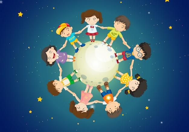 地球の上に立っている間子供たちが手を取り合って
