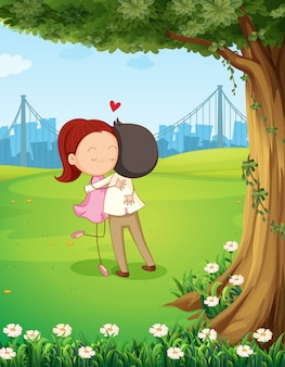木の近くでお互いを抱き締めるカップル