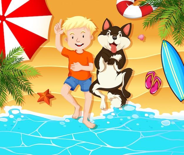少年と犬がビーチで休んで