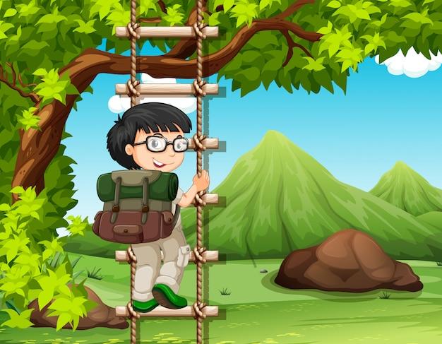 少年は公園で木のはしごを登る