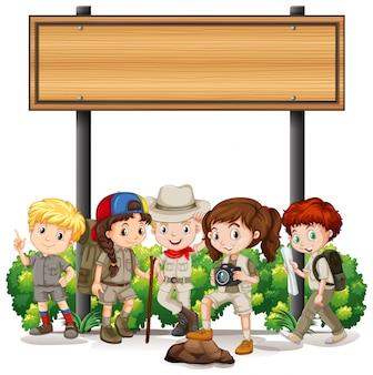 木製看板の下で子供たちとバナー