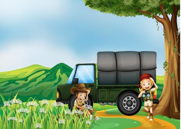 緑のトラックの横にいる少女と少年