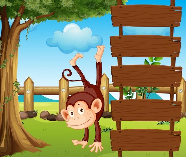 空の木製看板の横にある類人猿