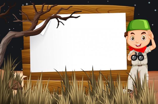 フィールドの少年と木製看板