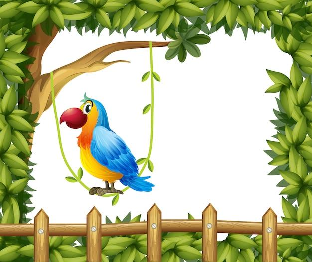 Попугай висит на виноградной лозе возле деревянного забора с рамой из листьев