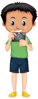 Мальчик в зеленой рубашке с цифровой камерой на белом