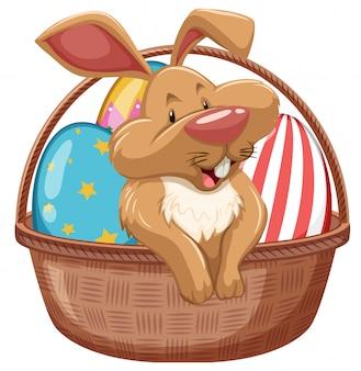 茶色のバスケットで飾られた卵をイースターのウサギ