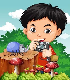Сцена с милым мальчиком фотографировать на жуков в парке