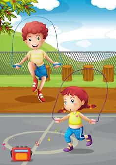Мальчик и девочка делают прыжки в парке
