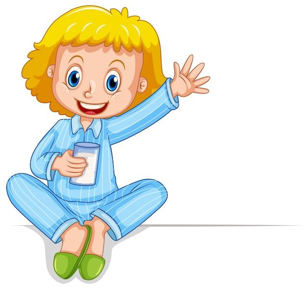ミルクのガラスを持っているパジャマの少女
