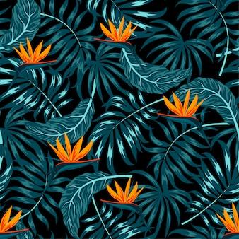 暗い背景に植物と花を持つ熱帯のシームレスパターン
