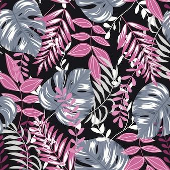 暗い背景に熱帯植物とトレンドのシームレスパターン