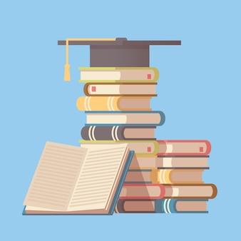 本の山に大学院の帽子。