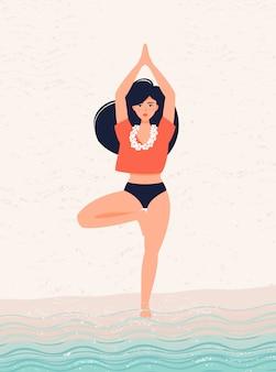 海沿いの木のポーズでヨガを練習するブルネットの少女