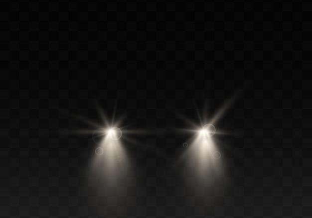 黒の背景にヘッドライトが付いている車のシルエット。