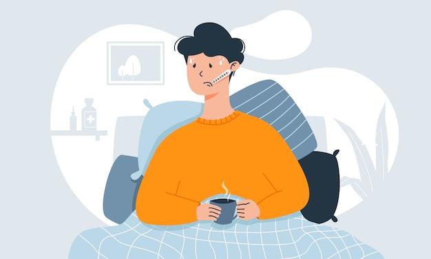 Молодой человек с такими симптомами простуды, как лихорадка, головная боль и боль в горле, измеряет температуру в постели и держит чашку чая.