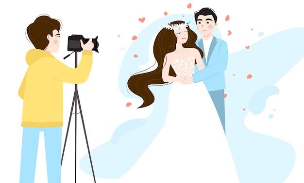 Невеста в белом платье и жених в свадебном костюме позирует фотографу. профессиональный фотограф с камерой на штативе.