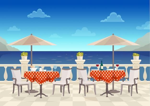 通りの海の景色を望むパラソルの下のテーブルがあるカフェ