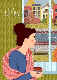 Женщина с чашкой чая смотрит в окно